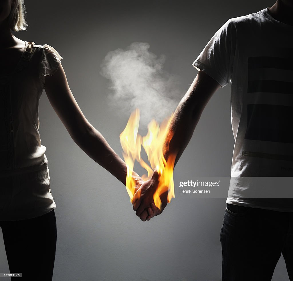 Couple holding hands which are engulfed in flames : Stock Photo
