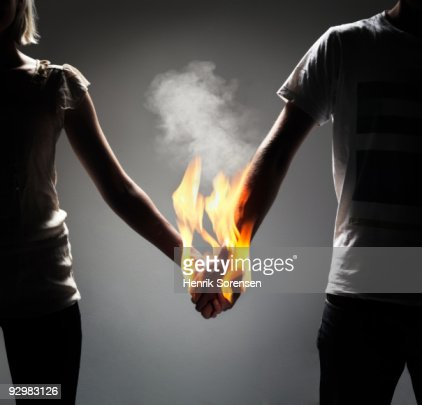 Couple holding hands which are engulfed in flames : Foto de stock