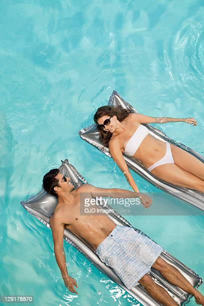 Couple holding hands while lying on raft