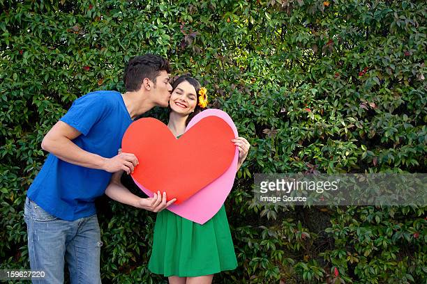 Couple holding heart shape, man kissing woman
