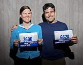 Couple holding marathon numbers, smiling, portrait