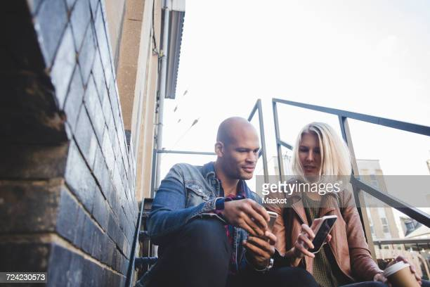 Couple holding mobile phones while sitting on steps in city