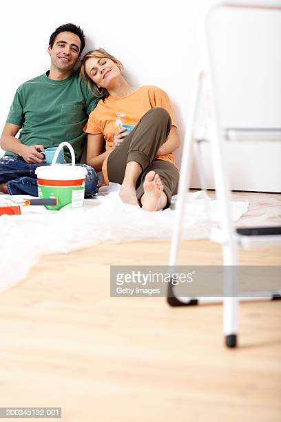 Couple holding mugs, sitting on floor by paint and step ladder
