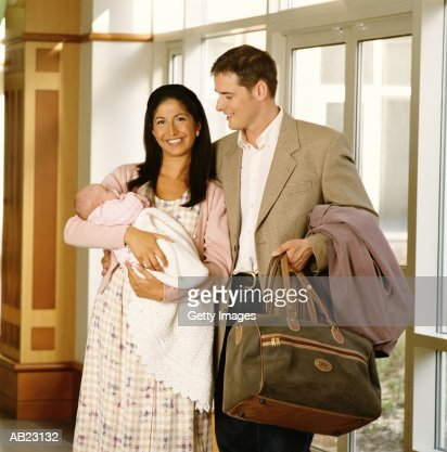 Couple holding newborn baby (0-3 months), leaving hospital : Stock Photo