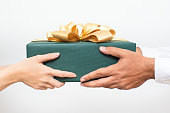 Close-up of couple holding packaged Christmas present together. Woman passing gift to boyfriend while congratulating him with New Year. Christmas gift-giving concept