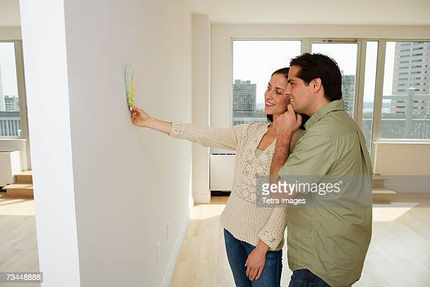 Couple holding paint swatches up to wall