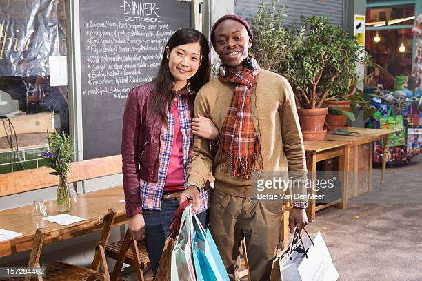 Couple holding shoppingbags in front of urban cafe