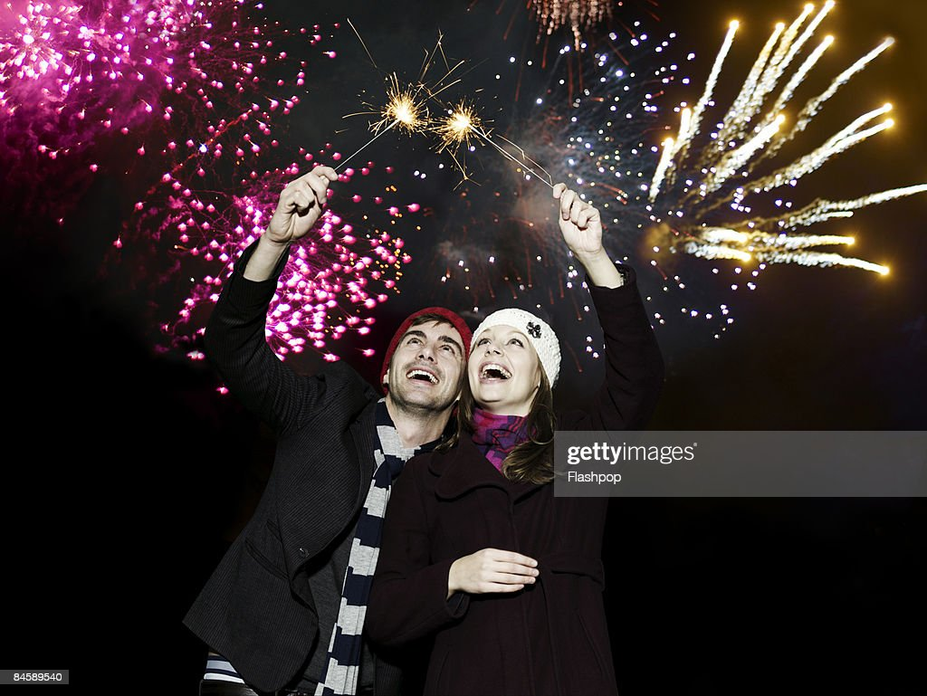 Couple holding sparklers at firework display : Stock Photo