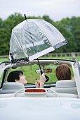 Couple holding umbrella inside a convertible