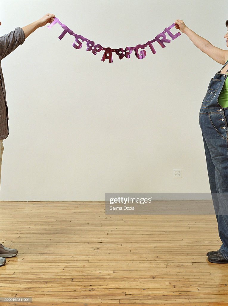Couple holding up 'It's a girl' sign in apartment : Stock Photo
