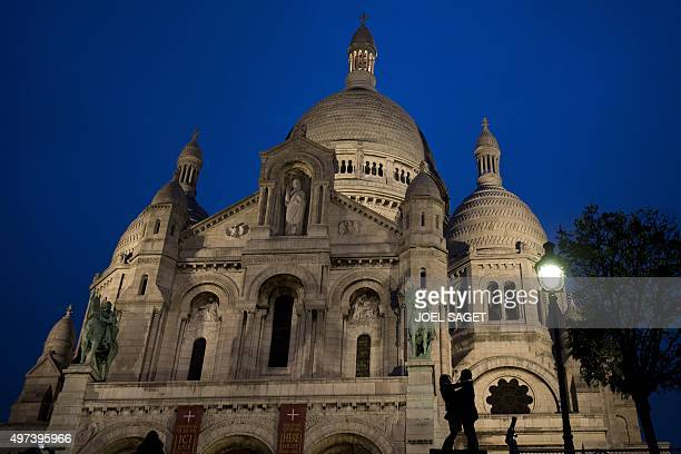 A couple holds each other in front of the Sacre Coeur Basilica on November 16 2015 in Paris three days after a series of deadly coordinated attacks...