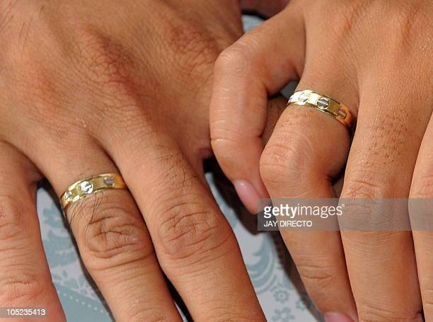 A couple holds hands showing their wedding rings during a mass wedding of 250 couple in Manila on October 10 2010 The date 10/10/10 sparked a wedding...