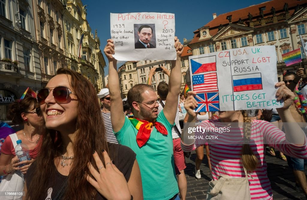 A couple holds up a placard with a picture of the Russian President Vladimir Putin made up as Hitler as they take part in the third gay pride festival in the Czech capital Prague on August 17, 2013. The placards read ' Putin? New Hitler?' and 'CZ, USA, UK Support LGBT, it does get better'.
