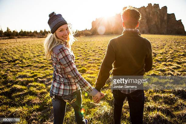 Couple holing hands and smiling.