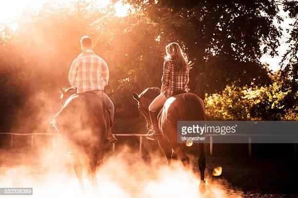 Couple horseback riding at sunset.