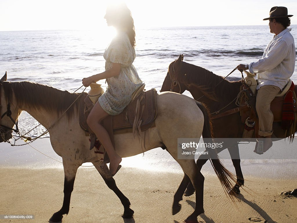 Couple horseback riding on beach, side view : Stock Photo