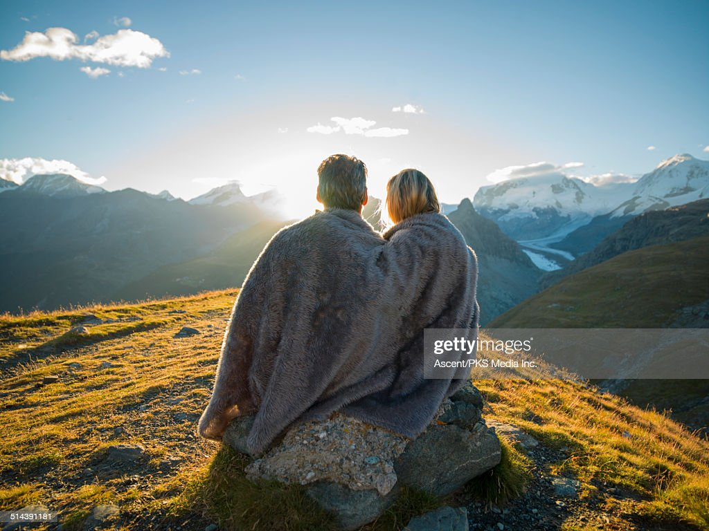 Couple huddle in blanket, watch mountain sunrise