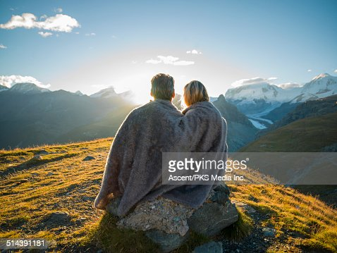Couple huddle in blanket, watch mountain sunrise
