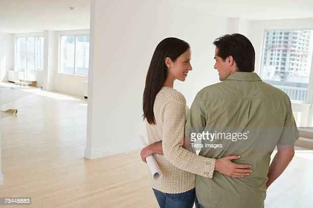 Couple hugging and holding blueprints in empty house