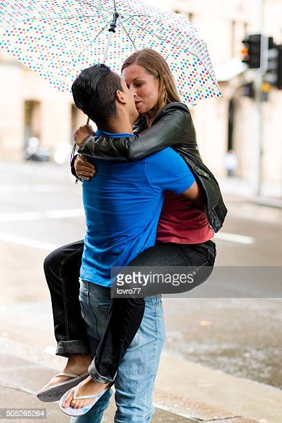 Couple hugging and kissing in rainy day