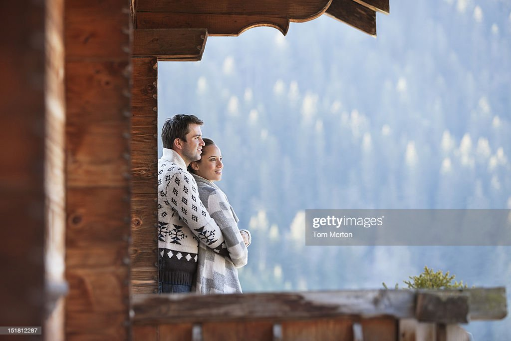 Couple hugging and looking at view from cabin porch : Stock Photo