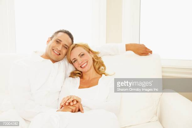 Couple hugging and smiling on sofa