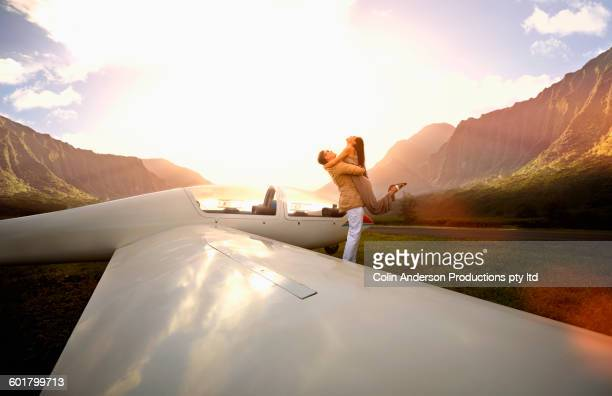 Couple hugging at glider airplane on remote runway