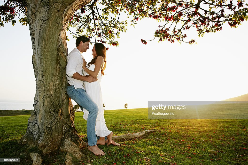 Couple hugging by tree in park : Stock Photo