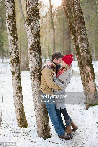 Couple hugging face to face in snowy woods