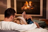 Young couple hugging on sofa in front of fireplace at home, rear view. Click here for more 'People at Home' images: