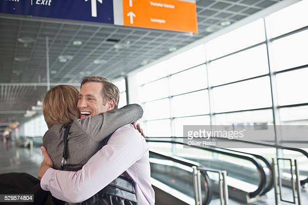 Couple hugging in airport terminal