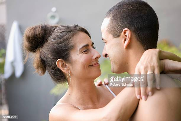 Couple hugging in backyard garden