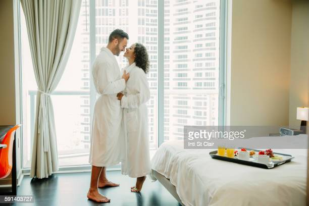 Couple hugging in bathrobes in hotel room