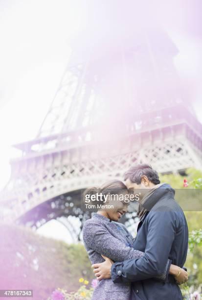 Coppia, abbracciare nella parte anteriore della Torre Eiffel, Parigi, Francia