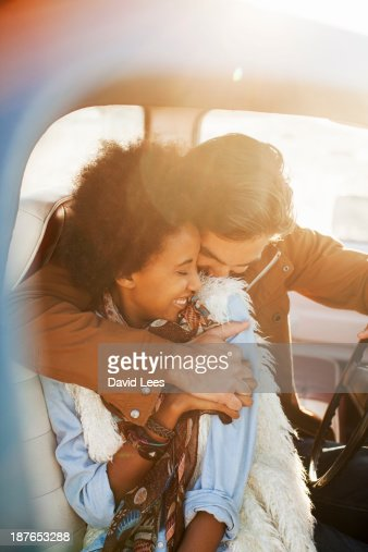 Couple hugging in front of truck