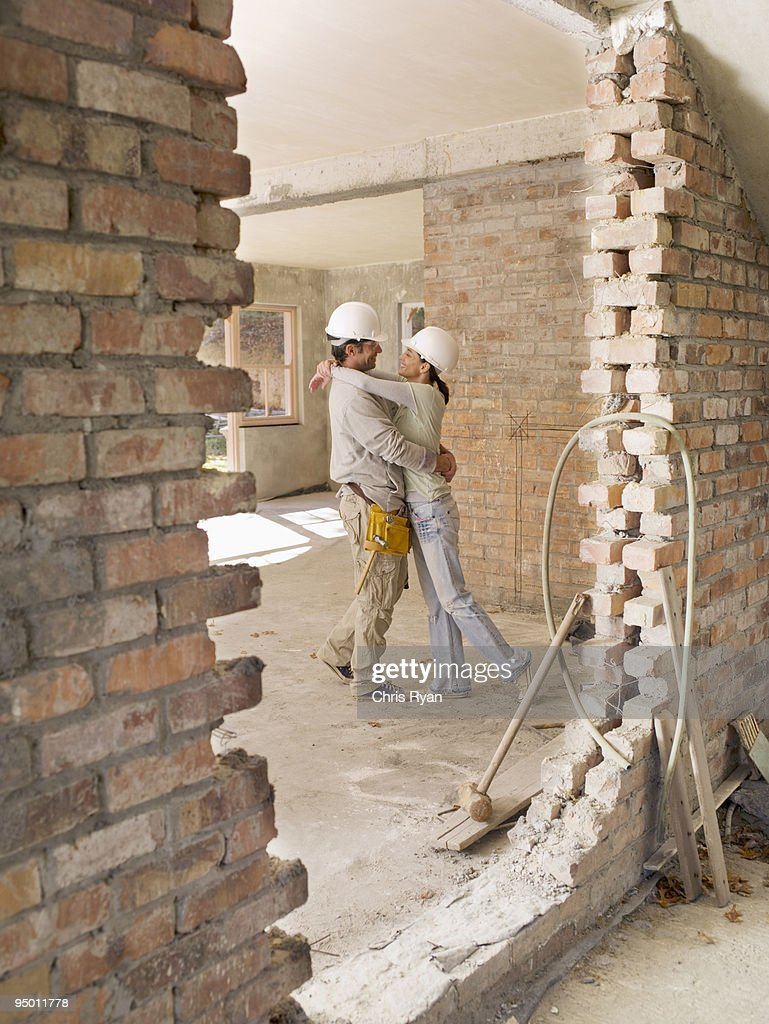 Couple hugging in house under construction : Stock Photo