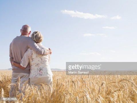 Couple hugging in remote wheat field : Stock Photo