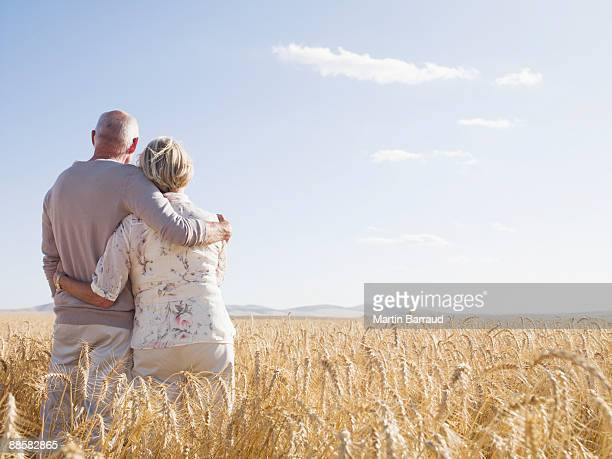 Couple hugging in remote wheat field