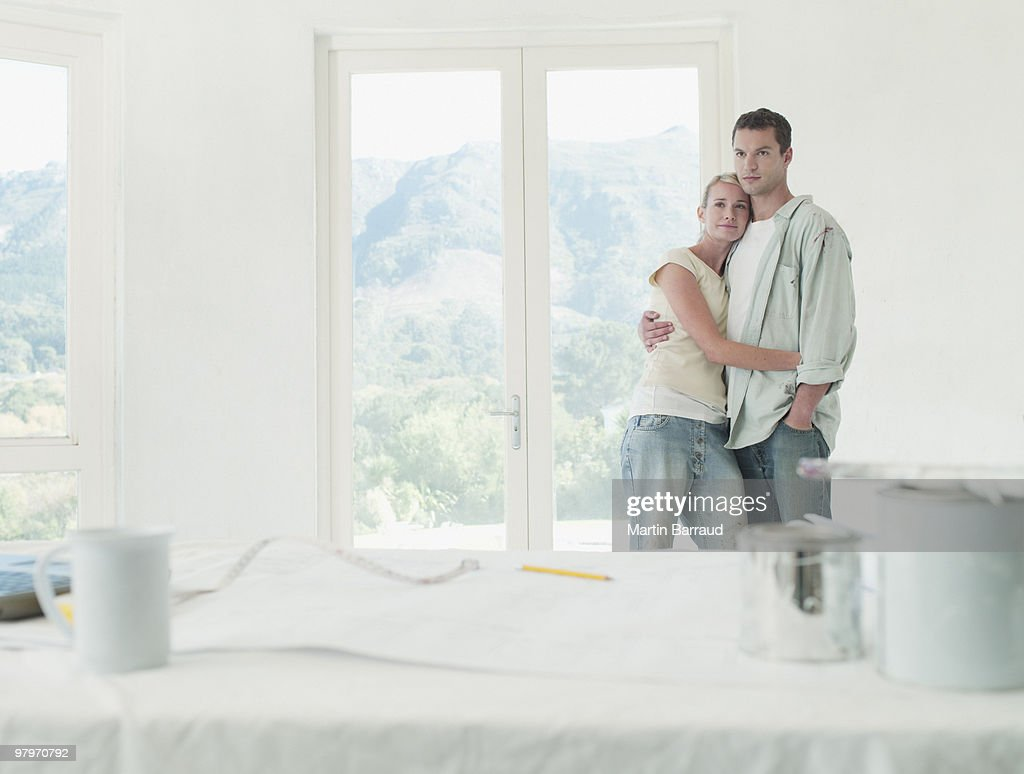 Couple hugging in room with drop cloths and paint cans : Stock Photo