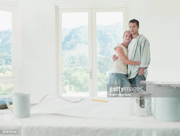 Couple hugging in room with drop cloths and paint cans
