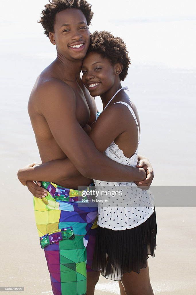Couple hugging in waves on beach : Stock Photo