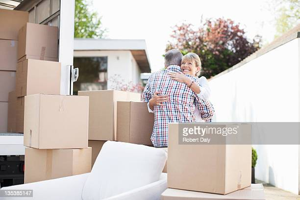 Couple hugging near boxes and moving van