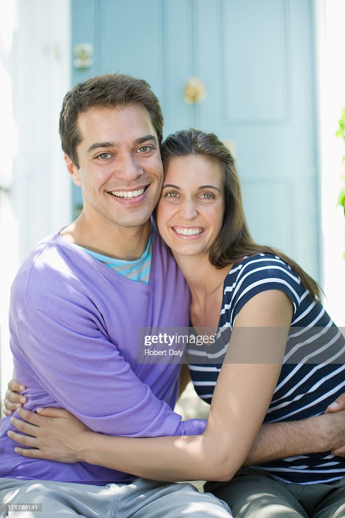 Couple hugging on front stoop : Stock Photo