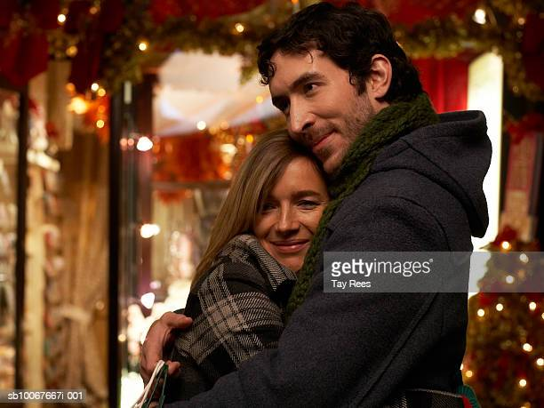 Couple hugging on street at night