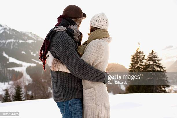 Couple hugging outdoors in snow