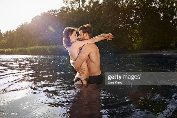 Couple hugging, standing in the water at lake