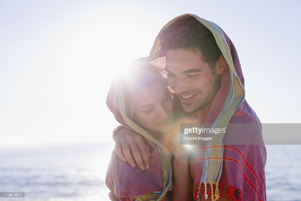 Couple hugging under blanket on beach : Stock Photo