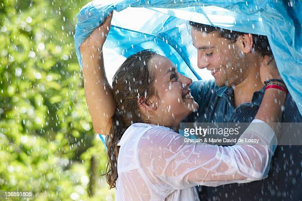 Couple hugging under cover in rain
