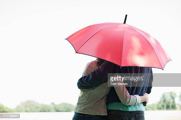 Couple hugging underneath red umbrella