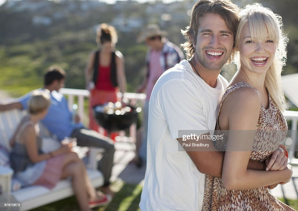 Couple hugging with friends at barbecue : Stock Photo